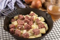 在生铁平底锅的未加工的咸牛肉马铃薯泥 免版税图库摄影