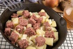 在生铁平底锅的未加工的咸牛肉马铃薯泥 免版税库存照片