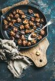在生铁平底锅的烤栗子在深蓝背景 免版税库存照片