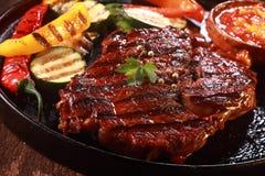 在生铁平底锅的烤牛排有菜的 库存照片