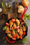 在生铁平底锅的烤鸡鼓槌 免版税库存图片