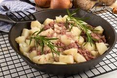 在生铁平底锅的煮熟的咸牛肉马铃薯泥 免版税库存图片