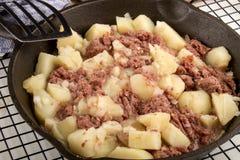 在生铁平底锅的煮熟的咸牛肉马铃薯泥 库存照片