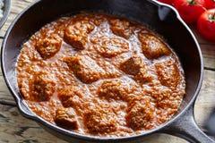 在生铁平底锅的马都拉斯黄油牛肉咖喱慢厨师印地安辣羊羔食物 库存照片