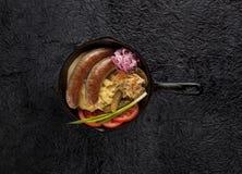 在生铁平底锅,顶视图的香肠 库存图片