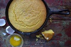 在生铁长柄浅锅的整个黄色玉米面包在土气木台式视图 库存图片