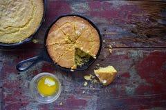 在生铁长柄浅锅的黄色玉米面包在土气木台式视图 免版税库存图片