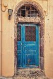 在生锈的墙壁上的蓝色门 库存图片