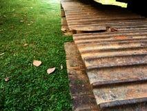 在生锈的履带牵引装置框架的反向铲挖掘机在草地在庭院里 库存图片