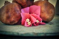 在生锈的盘子和花的石榴果子 免版税图库摄影