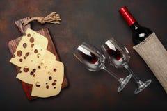 在生锈的背景的一个切板和maasdam乳酪切的瓶酒、两块玻璃 库存照片