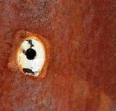 在生锈的金属板的一个孔 库存图片