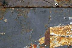 在生锈的金属的灰色油漆与被剥皮的肮脏的纸7 免版税库存图片