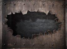 在生锈的金属蒸汽废物背景的被撕毁的孔 免版税库存照片