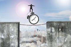 在生锈的链子的商人平衡的闹钟连接了concr 库存图片