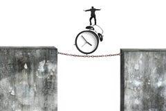 在生锈的链子的商人平衡的闹钟连接了concr 免版税库存照片