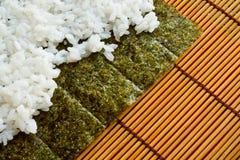 在生鱼片板料的米  免版税库存照片