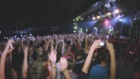 在生活摇滚乐音乐会鼓掌的人们在夜总会 执行在阶段的带 歌手,吉他弹奏者 股票录像
