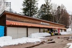 在用与杉木的雪和不生叶的树在背景中包括在Fukidashi的基础上的闭合的零售店停放 免版税库存照片