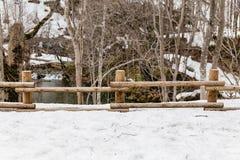 在用与湖的雪和不生叶的树在背景中包括在Fukidashi的基础上的木日志篱芭停放 免版税库存图片