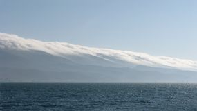 在用云彩盖的山的海景 免版税库存照片