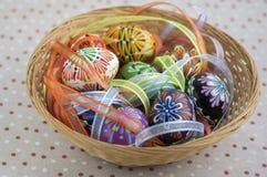 在用五颜六色的丝带盖的棕色柳条筐,传统复活节静物画的五颜六色的被绘的复活节彩蛋 免版税库存照片