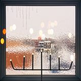 在用光装饰的一个结霜的窗口的冰柱 图库摄影