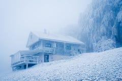 在用冰盖的山的老小屋在短的暴风雪以后 库存图片