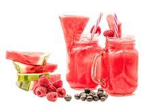 在用切片装饰的金属螺盖玻璃瓶的西瓜圆滑的人西瓜、莓、蓝莓和在白色隔绝的冰块 库存图片