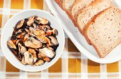在用卤汁泡的淡菜上添面包 免版税库存图片