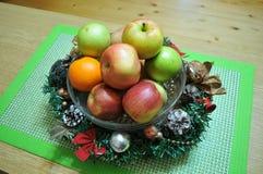 在用圣诞节装饰装饰的篮子的五颜六色的秋天苹果 图库摄影