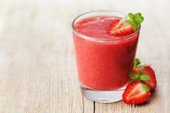 在用在土气背景,新鲜水果汁,戒毒所食物的薄荷叶装饰的玻璃的草莓圆滑的人 库存图片