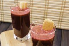 在用在被定调子的木盘子和竹子背景选择聚焦的红萝卜切片装饰的玻璃的新鲜的红萝卜和甜菜根汁 库存照片