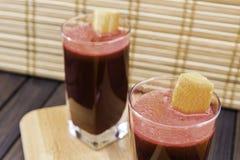 在用在被定调子的木盘子和竹子背景选择聚焦的红萝卜切片装饰的玻璃的新鲜的红萝卜和甜菜根汁 免版税库存照片