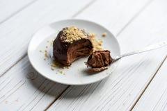 在用坚果装饰的一张白色桌上的开胃巧克力乳酪蛋糕 免版税库存照片