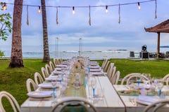 在用壳装饰的海滩附近设置白色的桌和水色蓝色结婚宴会 库存照片