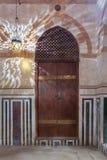 在用大理石盘区和灯笼阴影装饰的石墙上的木被成拱形的门在墙壁,老开罗,埃及上 库存照片
