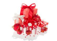 在用弓装饰的五颜六色的箱子,在白色隔绝的玩具球的圣诞节礼物 库存图片
