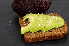 在用新被切的avocad做的黑暗的黑麦面包的鲕梨三明治 免版税图库摄影