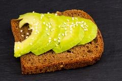 在用新被切的avocad做的黑暗的黑麦面包的鲕梨三明治 库存照片