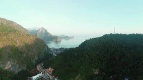 在用日出时间的热带森林盖的山之间的空中寄生虫飞行 与小船的热带天堂海湾 影视素材