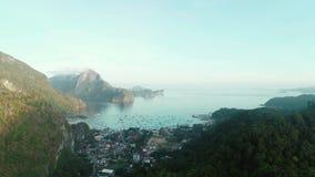 在用日出时间的热带森林盖的山之间的空中寄生虫飞行 与小船的热带天堂海湾 股票录像