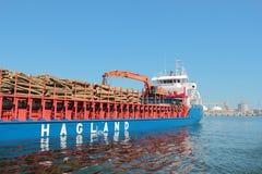 在用日志装载的口岸的船 库存照片