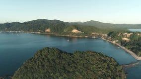 在用日落时间的热带森林盖的海岛的空中寄生虫飞行 与小船的热带天堂海湾在 影视素材
