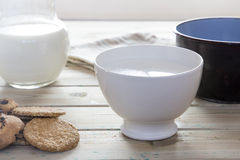 在用早餐的碗的平底深锅倾吐的牛奶 免版税图库摄影