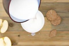 在用早餐的碗的平底深锅倾吐的牛奶 免版税库存图片