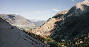 在用杉木森林盖的令人惊讶的白色山岩石土坎上的寄生虫飞行在夏天优胜美地国立公园地平线 股票录像