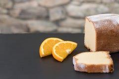 在用橙色fr两pices装饰的屋顶板岩的柠檬蛋糕  库存图片