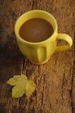 在用秋天叶子装饰的木桌上的咖啡 免版税库存照片
