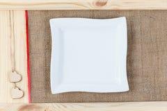 在用粗麻布报道的木头背景的心脏,一块白方块板材一张卡片为华伦泰` s天 库存照片